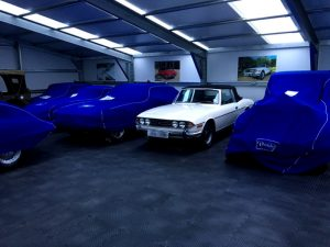 An image of prestige and classic luxury cars being stored in dust proof covers on a duramat floor