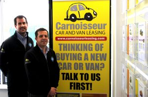 Elliot and Shaun from Cambridge Carnoisseur Leasing Store standing in front of the new yellow banner to promote the new leasing they do