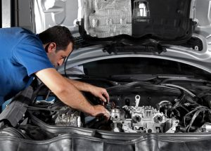 Man working on car removing components from engine bay to carry out repairs