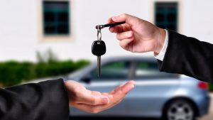 car leasing keys being handed over to customer for their new car parked in the back ground ready to drive off