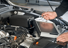 A tablet being used to read codes on a car on a workshop being held by a mechanic who is holding a pen to tap in the details to the table to gain the results needed to fix the car