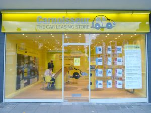carnoisseur shop front in yellow and glass with desks inside for clients to sit and discuss lease deals and offers