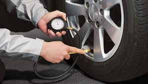 A person is checking their tyre pressures with a round pressure gauge to check correct pressure in the tyre