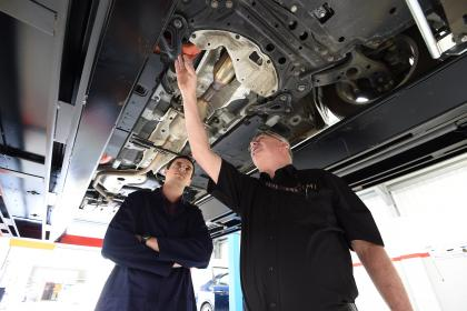 two men working on a MOT car checking for faults and advising on condition and safety of the vehicle to be on the road