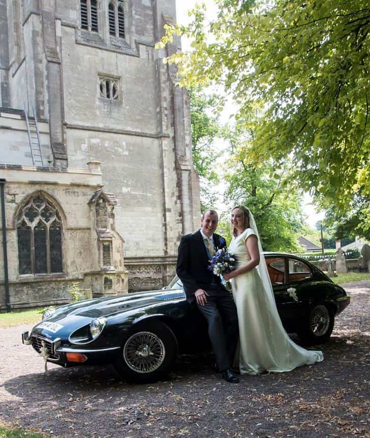 Bride and Groom sititng on their Jaguar E type Wedding car.