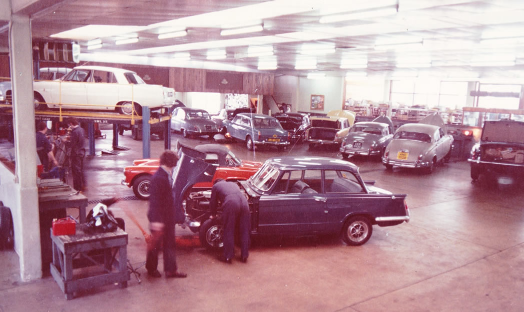 Image of people working on a classic car back in the original walls and son site.